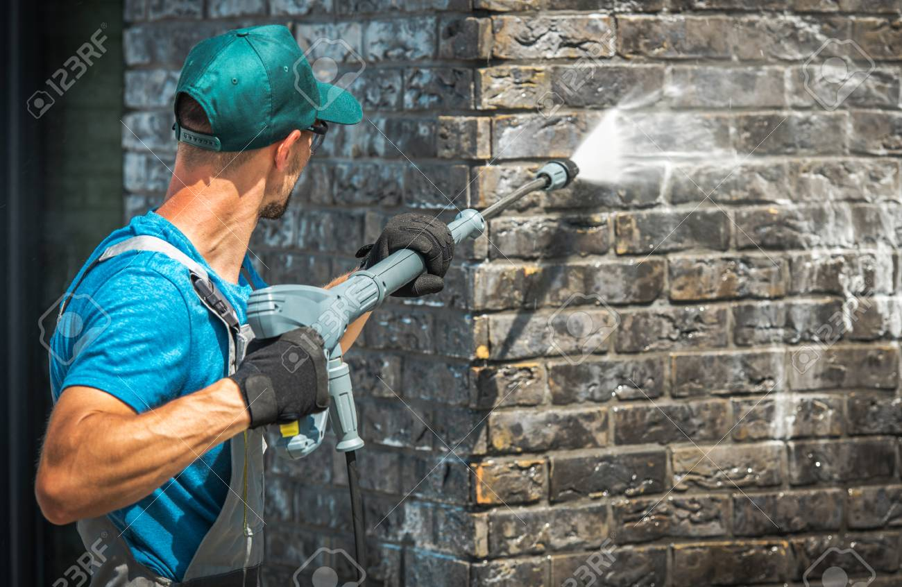 House Brick Wall Washing Using Pressure Washer. Caucasian Worker in His 30s. - 109893261