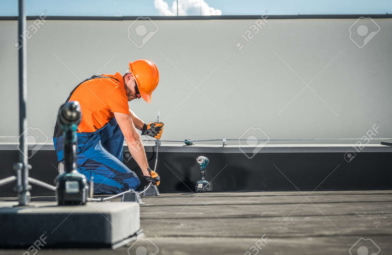 Caucasian Residential Building Lightning Protection System Installer in His 40s Finishing His Work on the Building Roof. - 156622421