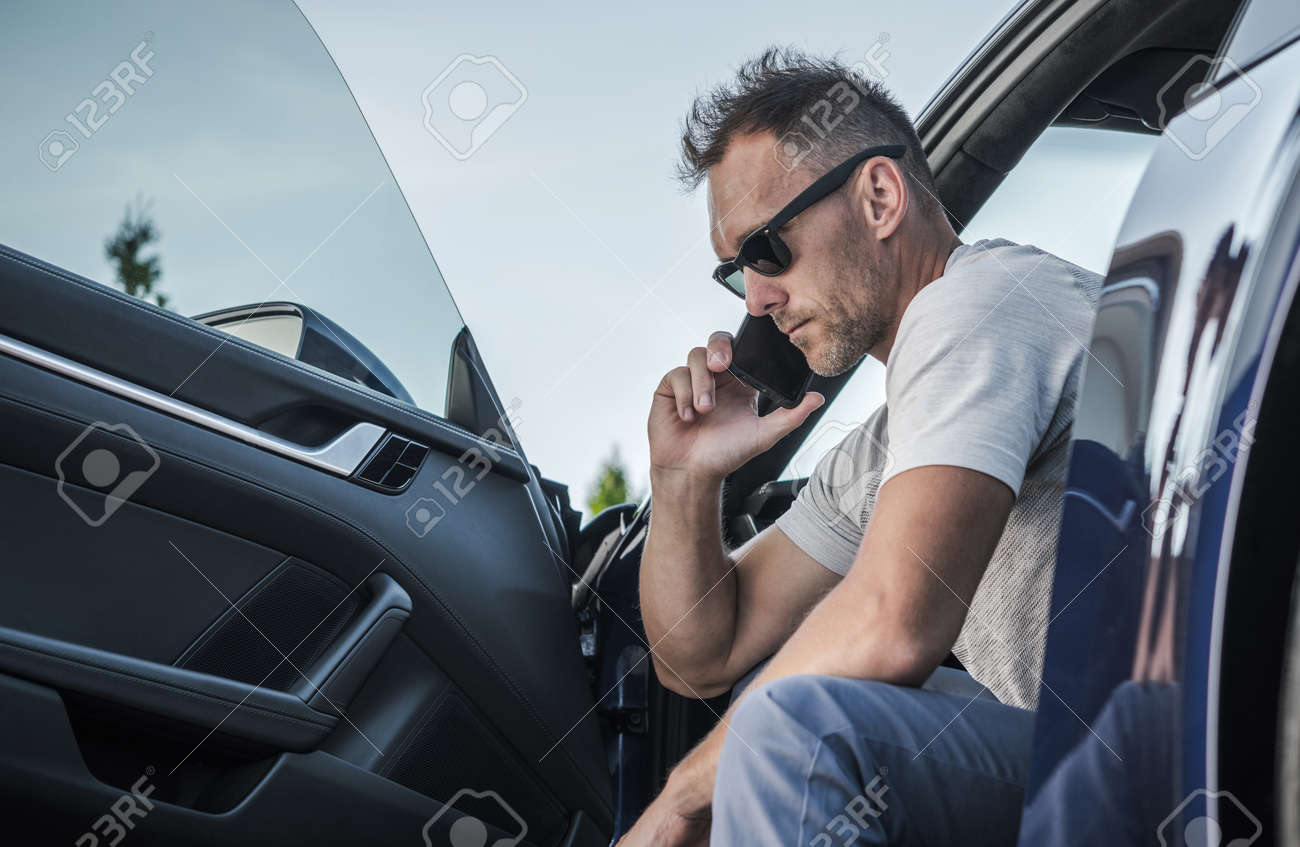 Caucasian Driver in His 40s Making Emergency Call From His Car. Calling Road Assistance. Transportation Industry Theme. - 165545842