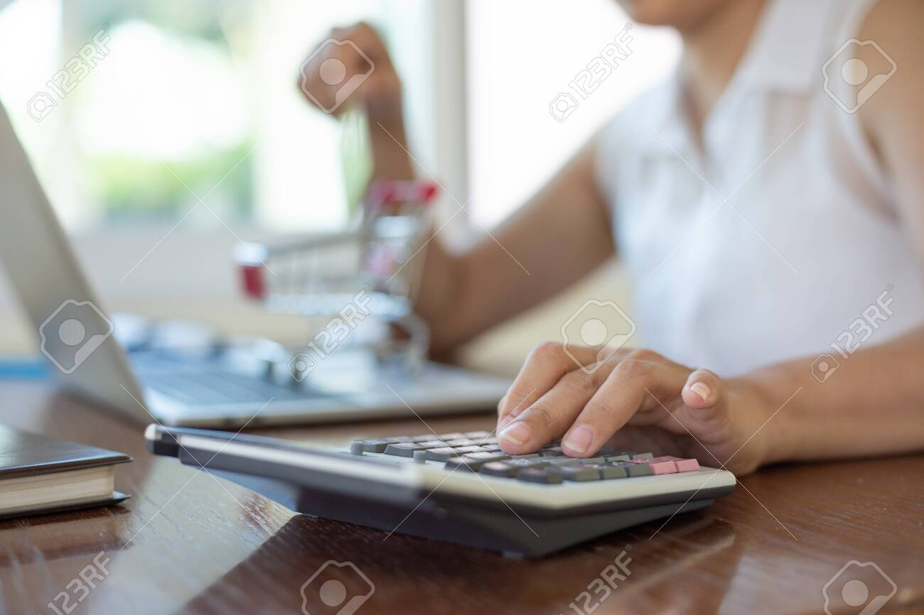 businesswomen using calculator and holding card for shopping online in home office.calculator concept - 143080937