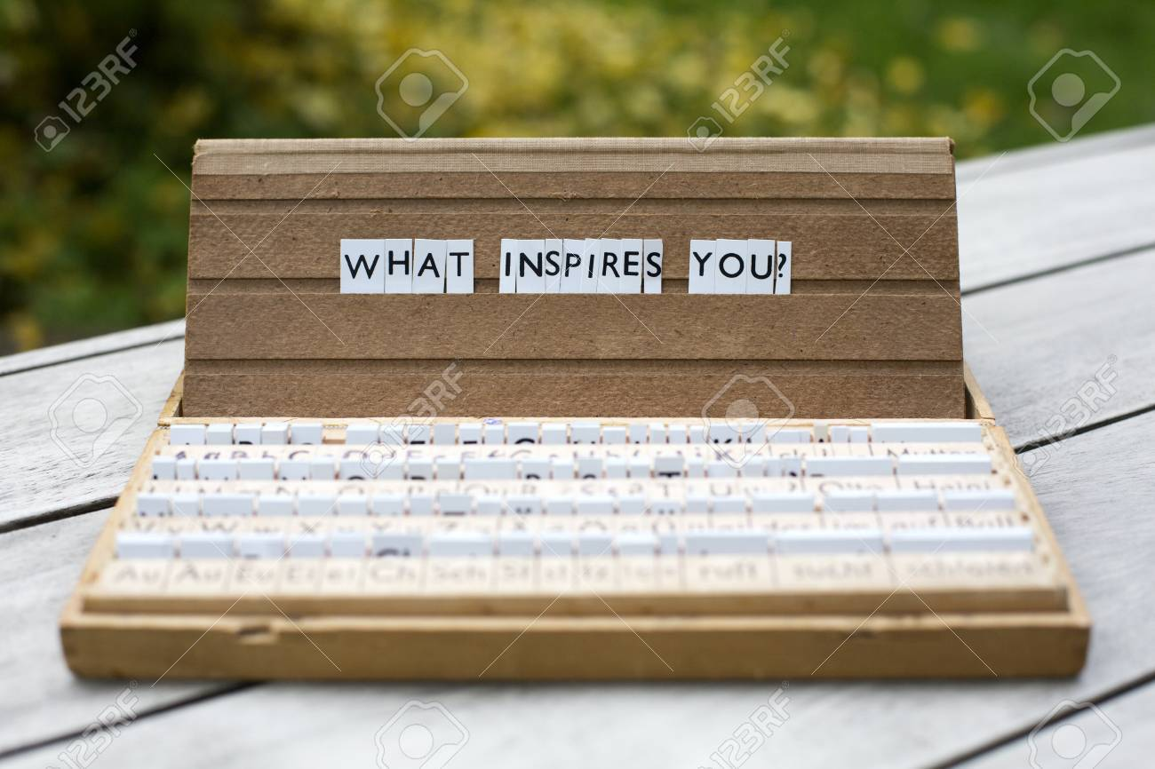 the words what inspires you on an old school letter box stock