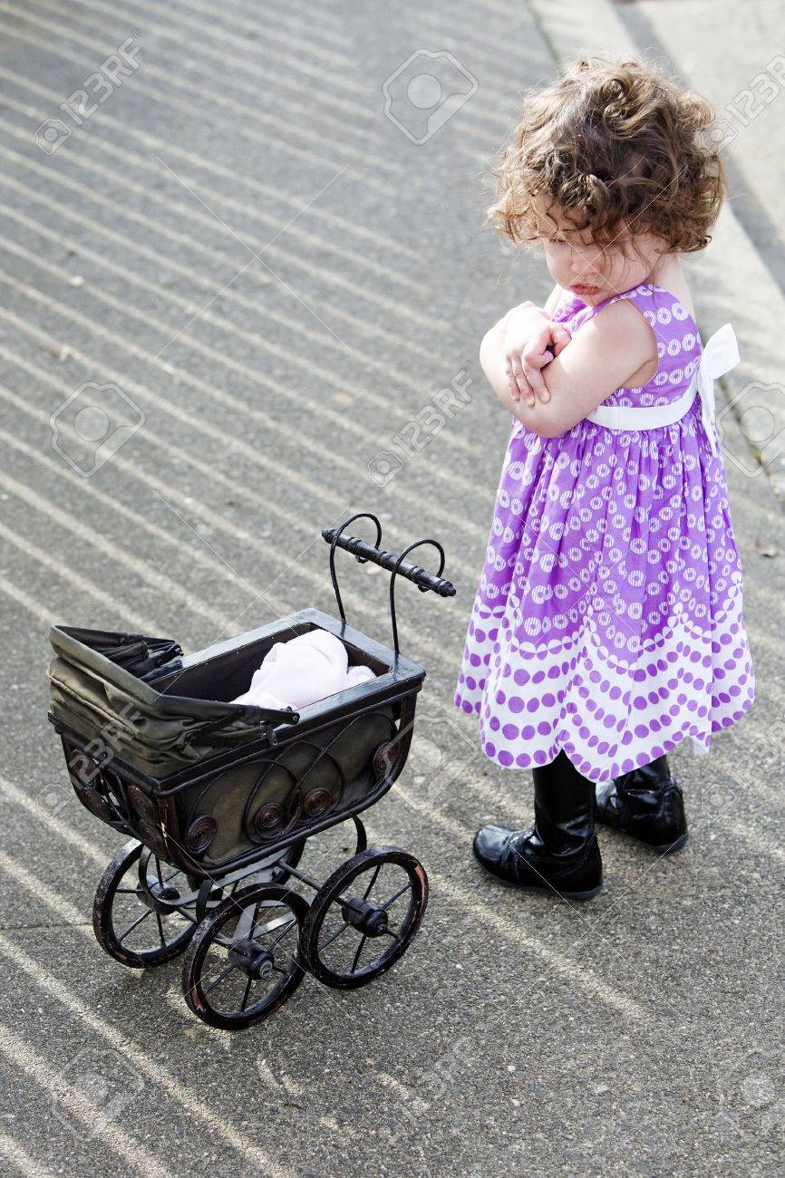 5dd23e6ac Little Girl With Pink Dress And Vintage Stroller Looking Sad.. Stock ...
