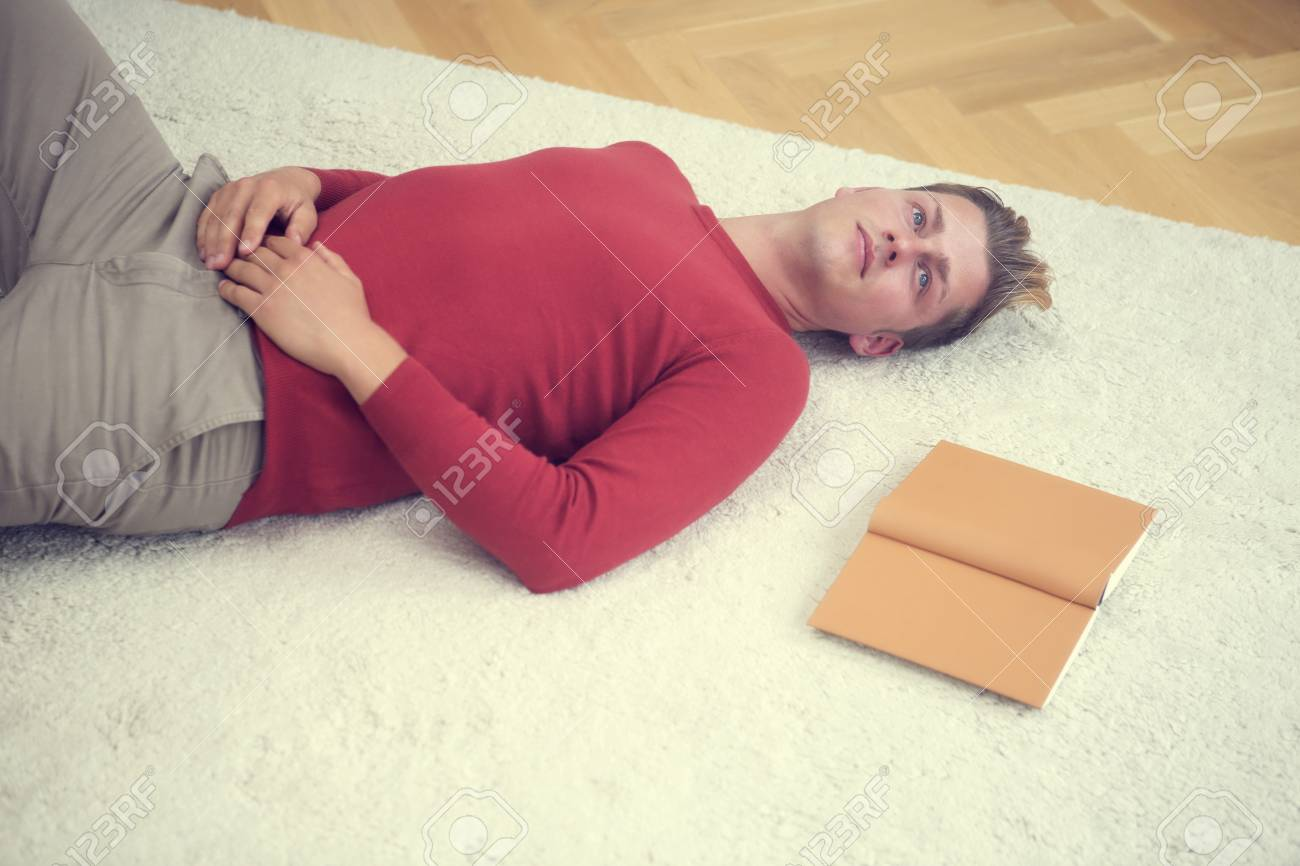 handsome blond man lying on carpet with a book - 65214229