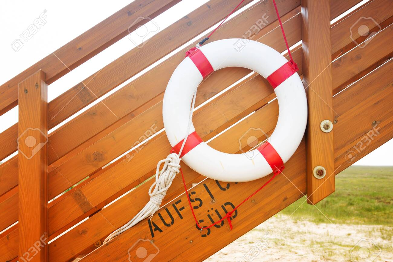 red and white life ring on wooden stairs by the beach