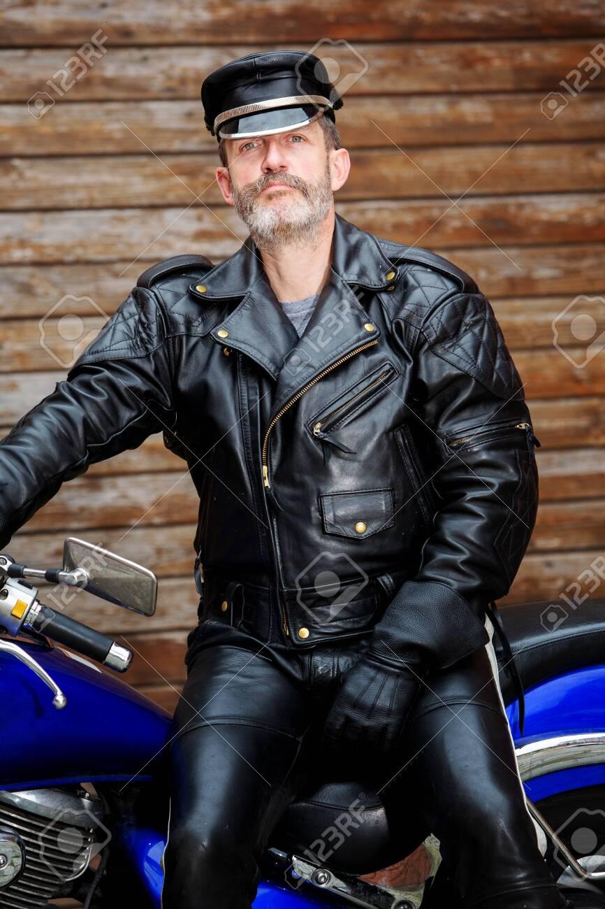 portrait of biker dressed in black leather sitting on his bike - 130064131