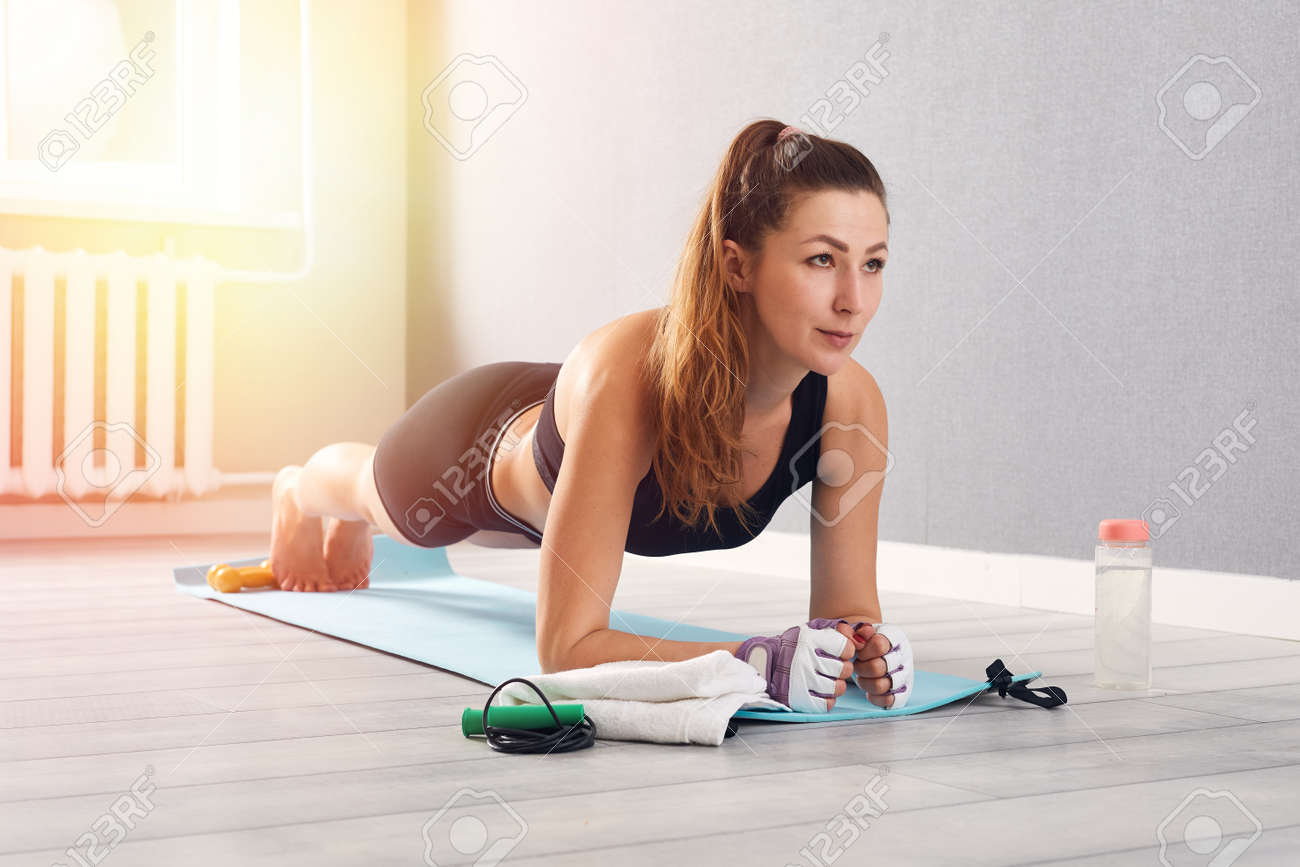 Woman In Fitness Wear Doing Exercise At Home. Time for yoga. healthy girl doing exercises while resting at home. Fitness, relaxation, stay home concept - 169825934