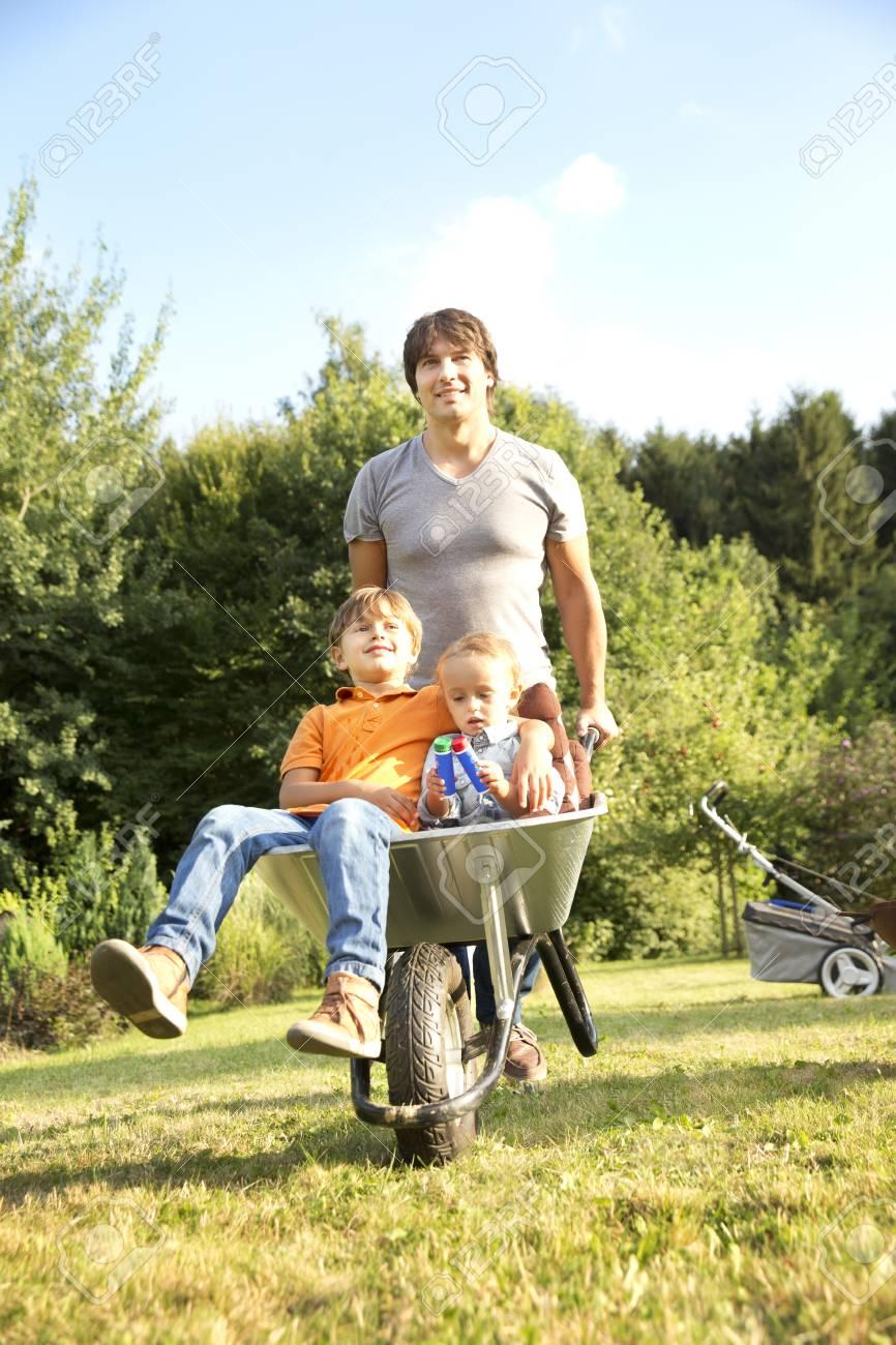 Father Pushing Two Sons In Wheelbarrow In Garden