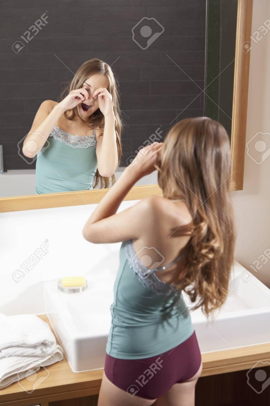 Salle De Bain Allemagne allemagne, bavière, jeune femme frottant les yeux devant le miroir de la  salle de bain