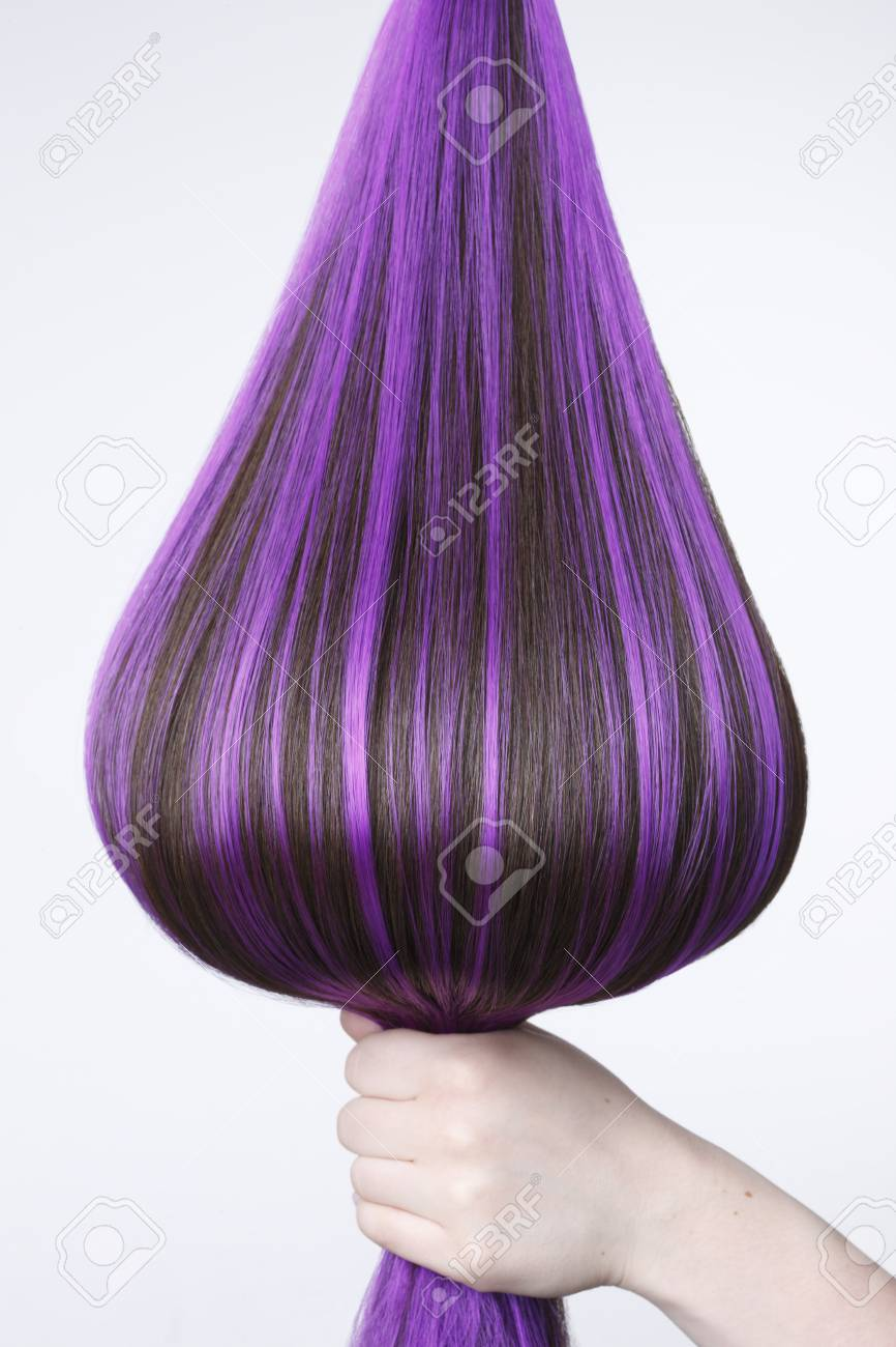 Human Hand Holding Brown Hair With Purple Highlights Against Stock