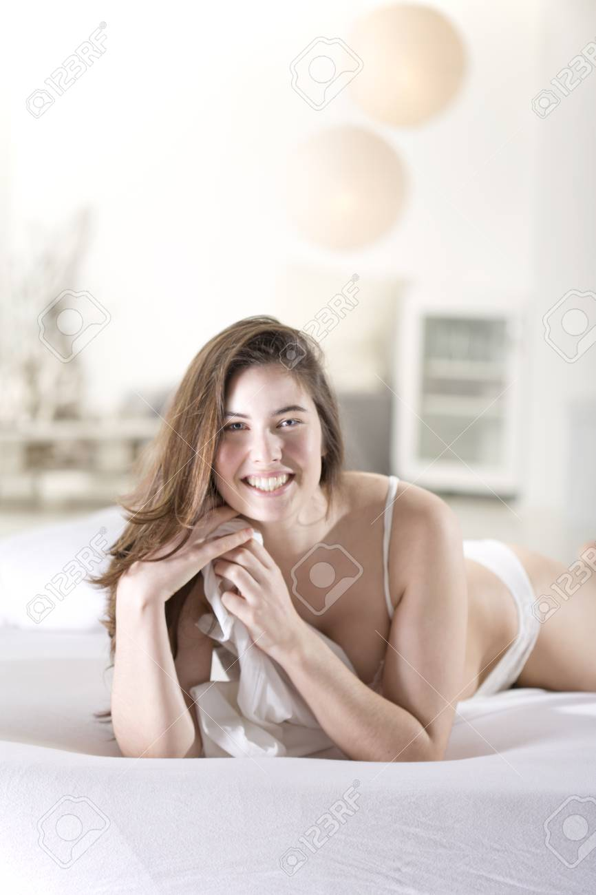 841e5028f16 Smiling young woman wearing white bra and panties lying on bed Stock Photo  - 90894077