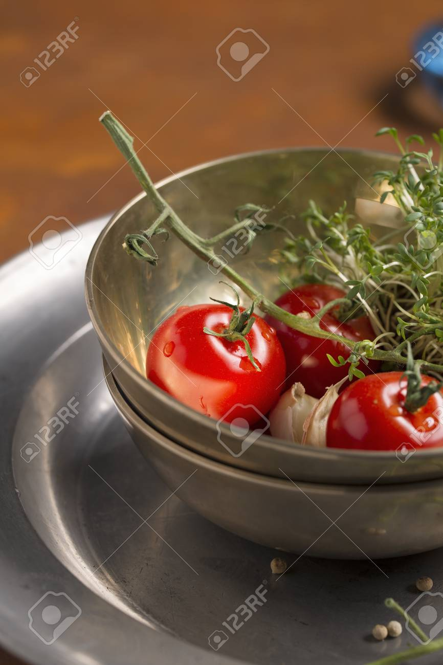 Tomatoes, Garden Cress And Garlic In A Bowl And Peppercorns On ...