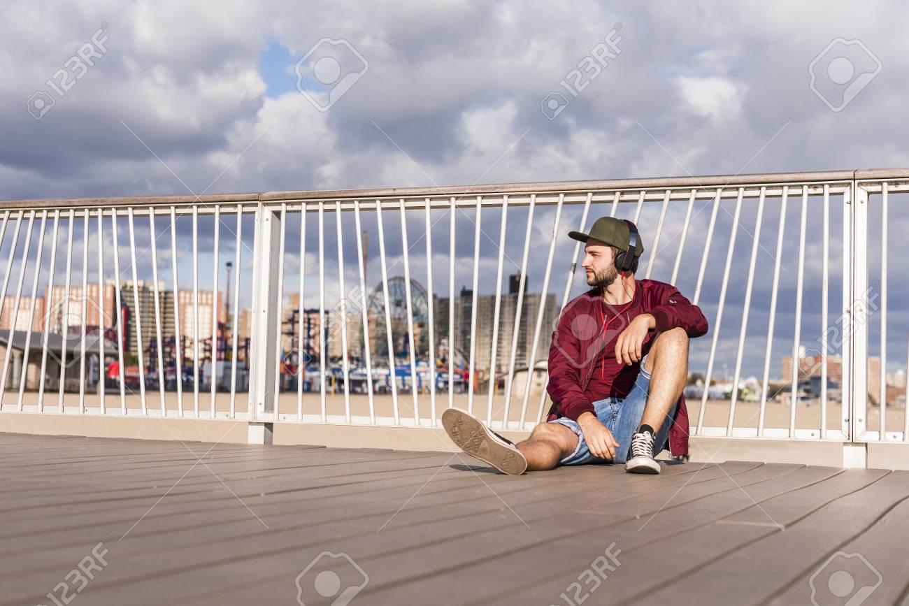 Usa New York City Man Sitting On Bridge On Coney Island Wearing