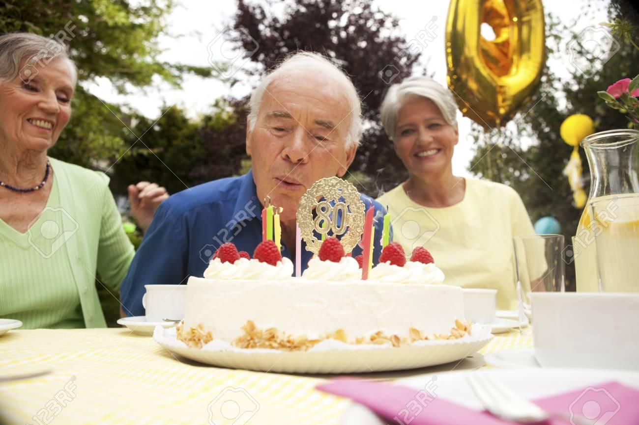 Senior Man Blowing Candle On 80th Birthday Cake Standard Bild
