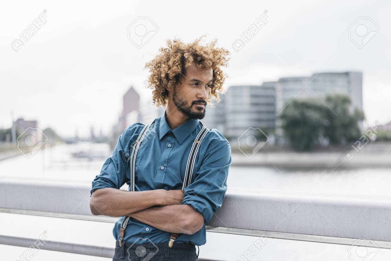 young man leaning on railing with arms crossed stock photo picture