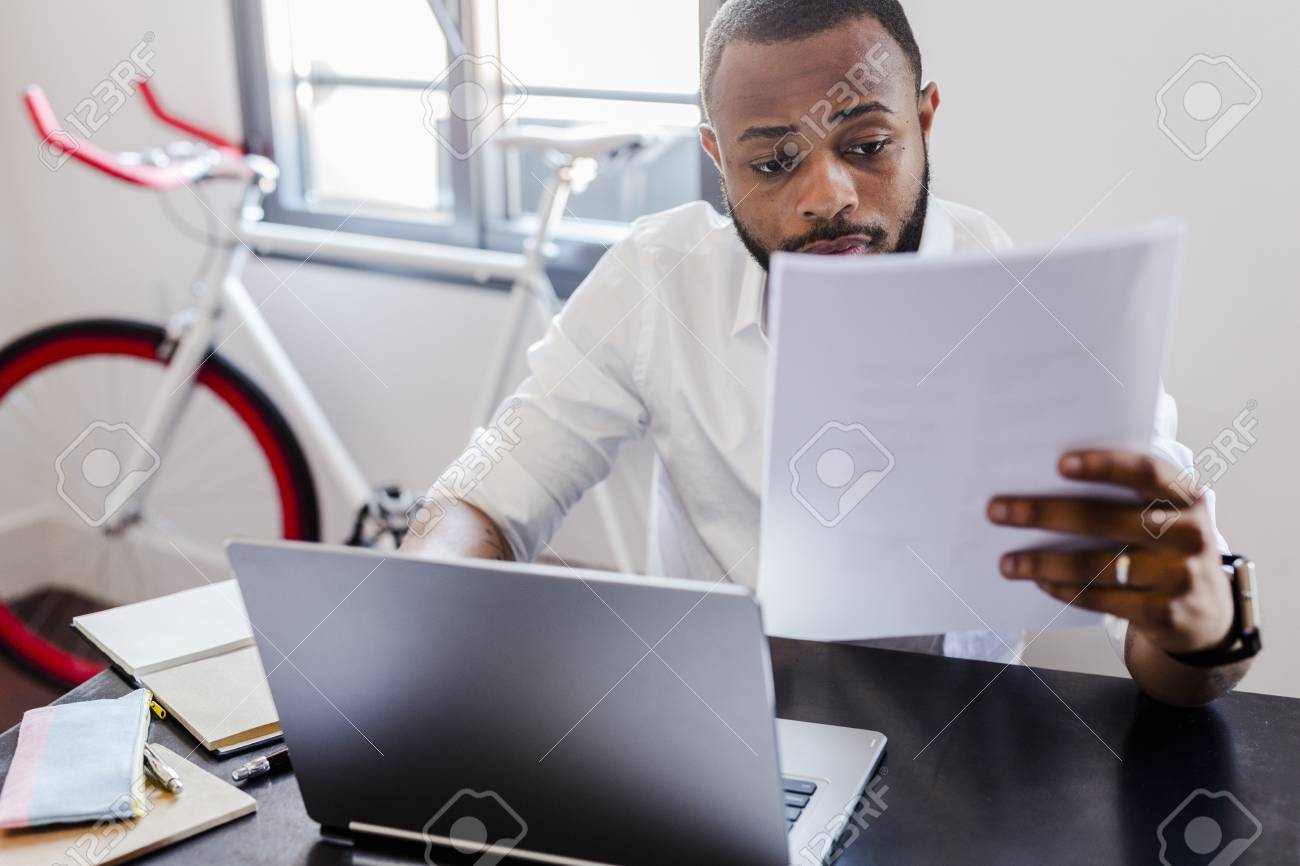 Man Looking At Papers At Desk In Home Office Stock Photo   96019929