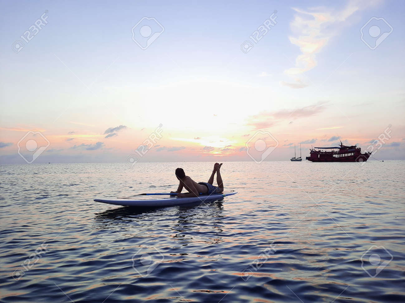 on a stand up paddle board, young man 34 years old, German, lies on a board on the ocean in Thailand, on the island Koh Tao at sunset - 169664543