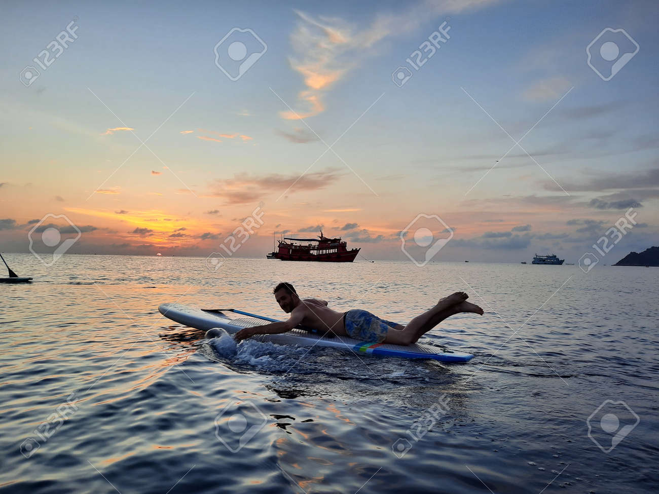 on a stand up paddle board, young man 34 years old, German, lies on a board on the ocean in Thailand, on the island Koh Tao at sunset - 169664552