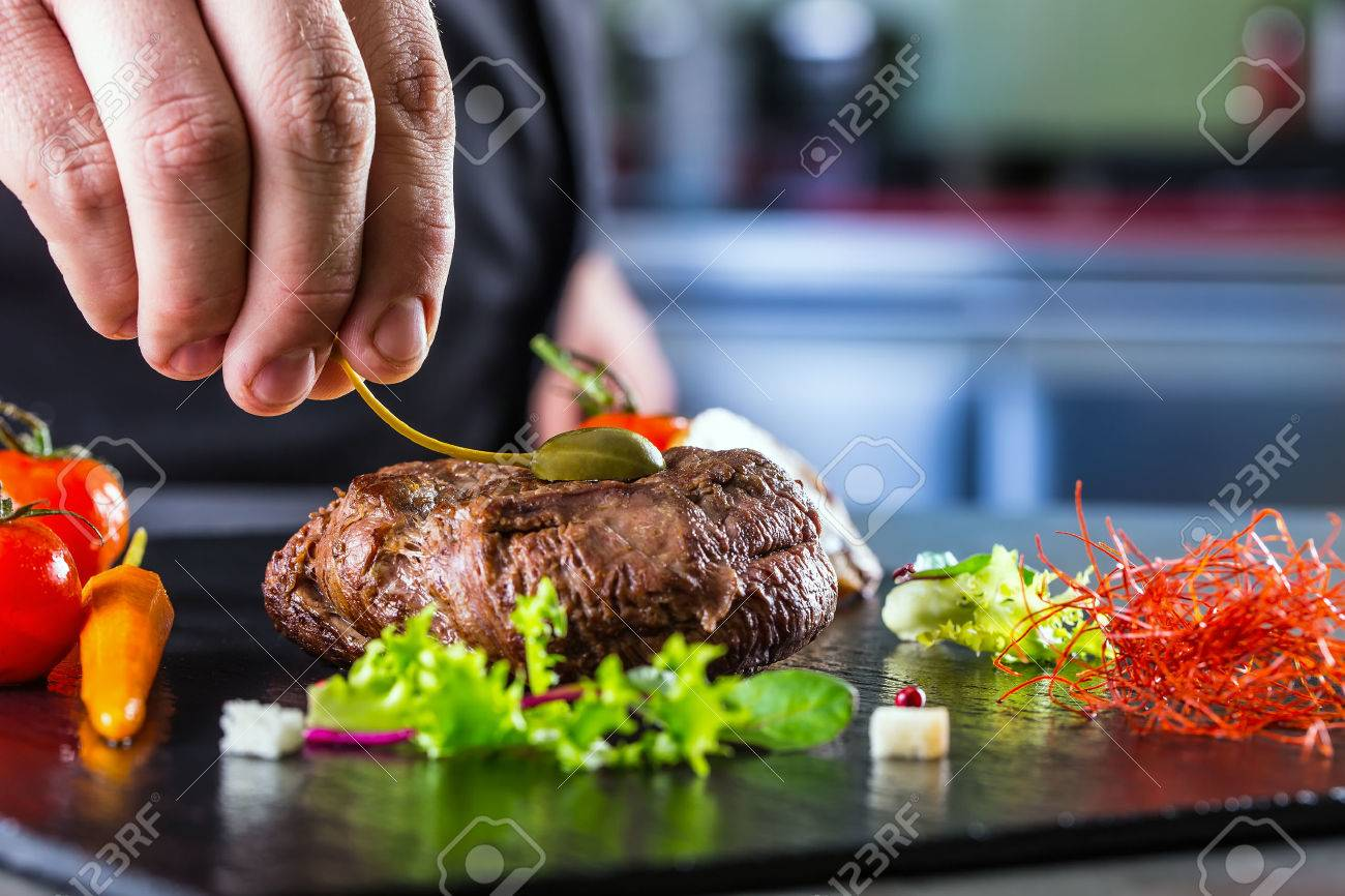 Chef in hotel or restaurant kitchen cooking only hands. Prepared beef steak with vegetable decoration - 39332843