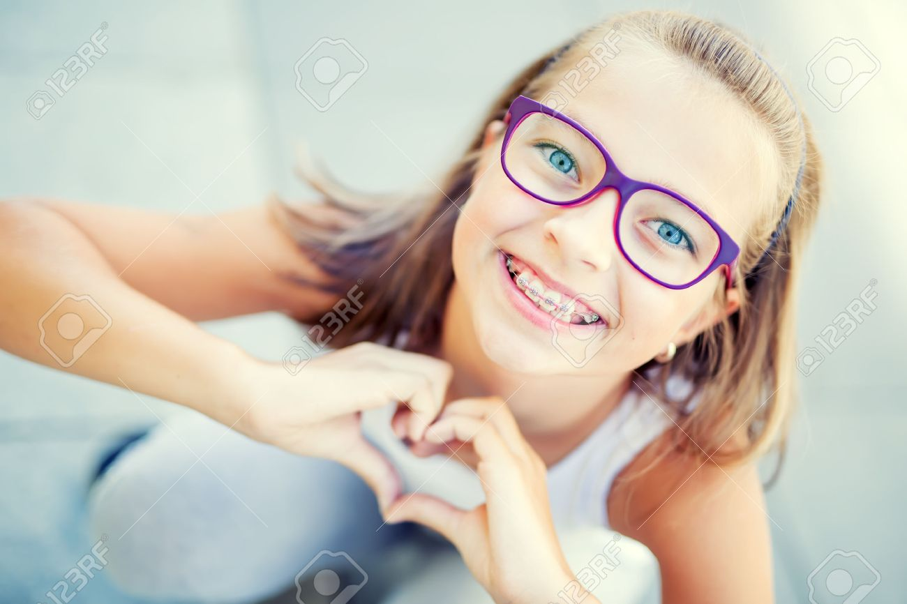 Smiling little girl in with braces and glasses showing heart with hands. - 62296726