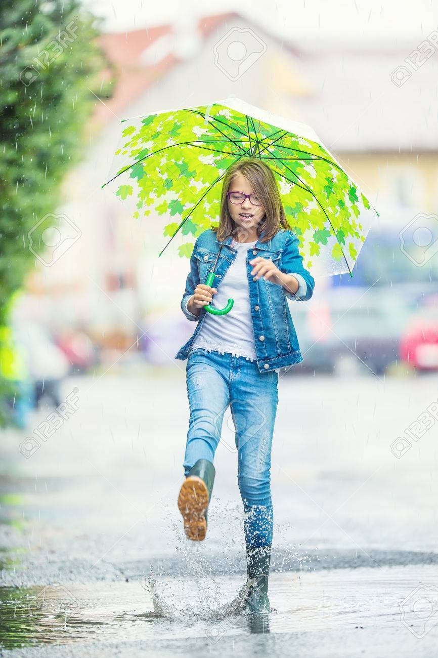 9ce69abec6f Portrait of beautiful young pre-teen girl with umbrella under rain. Stock  Photo -