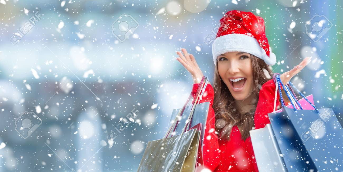 Christmas shopping. Attractive happy girl with credit card and shopping bags in santa hat. Snowy atmosphere. - 90608015