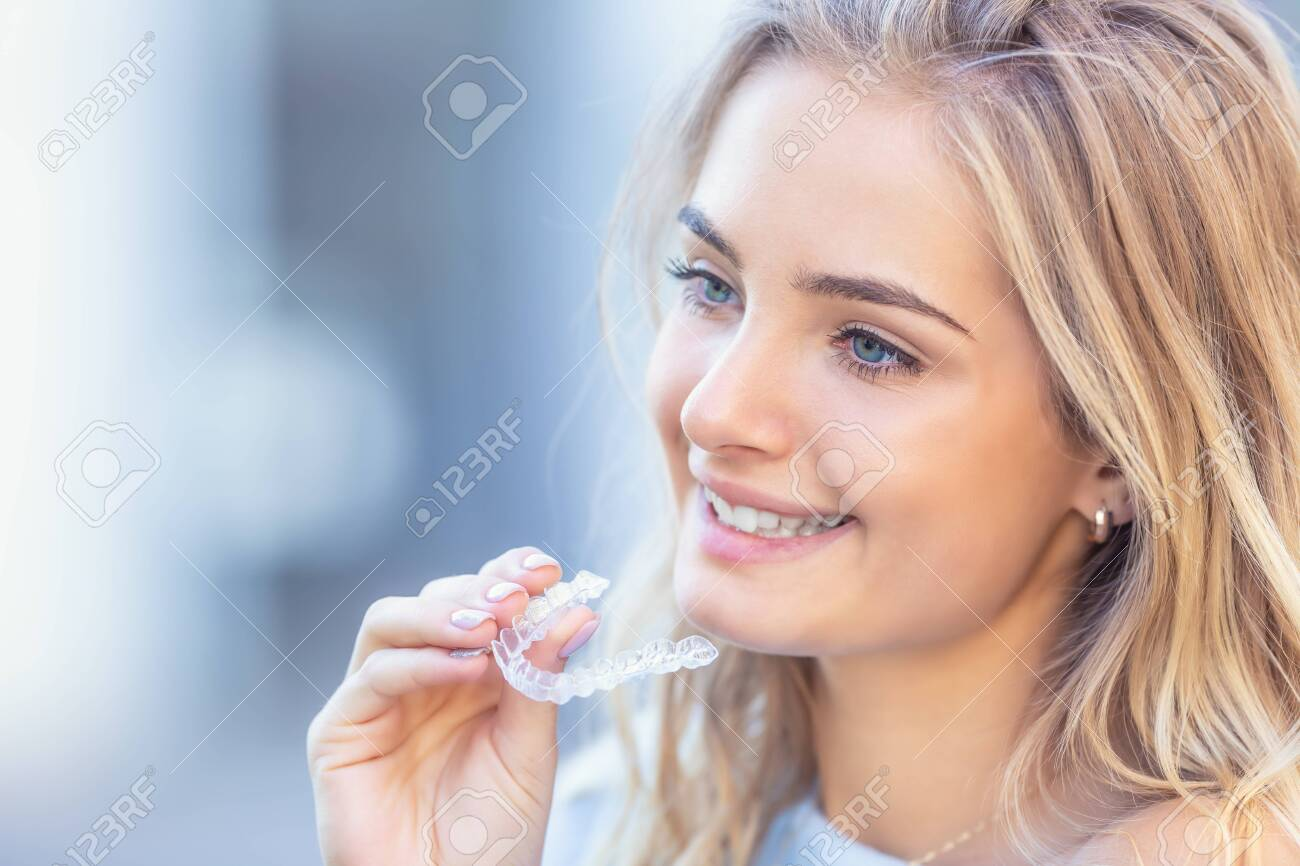 Invisalign orthodontics concept - Young attractive woman holding - using invisible braces or trainer. - 129669414