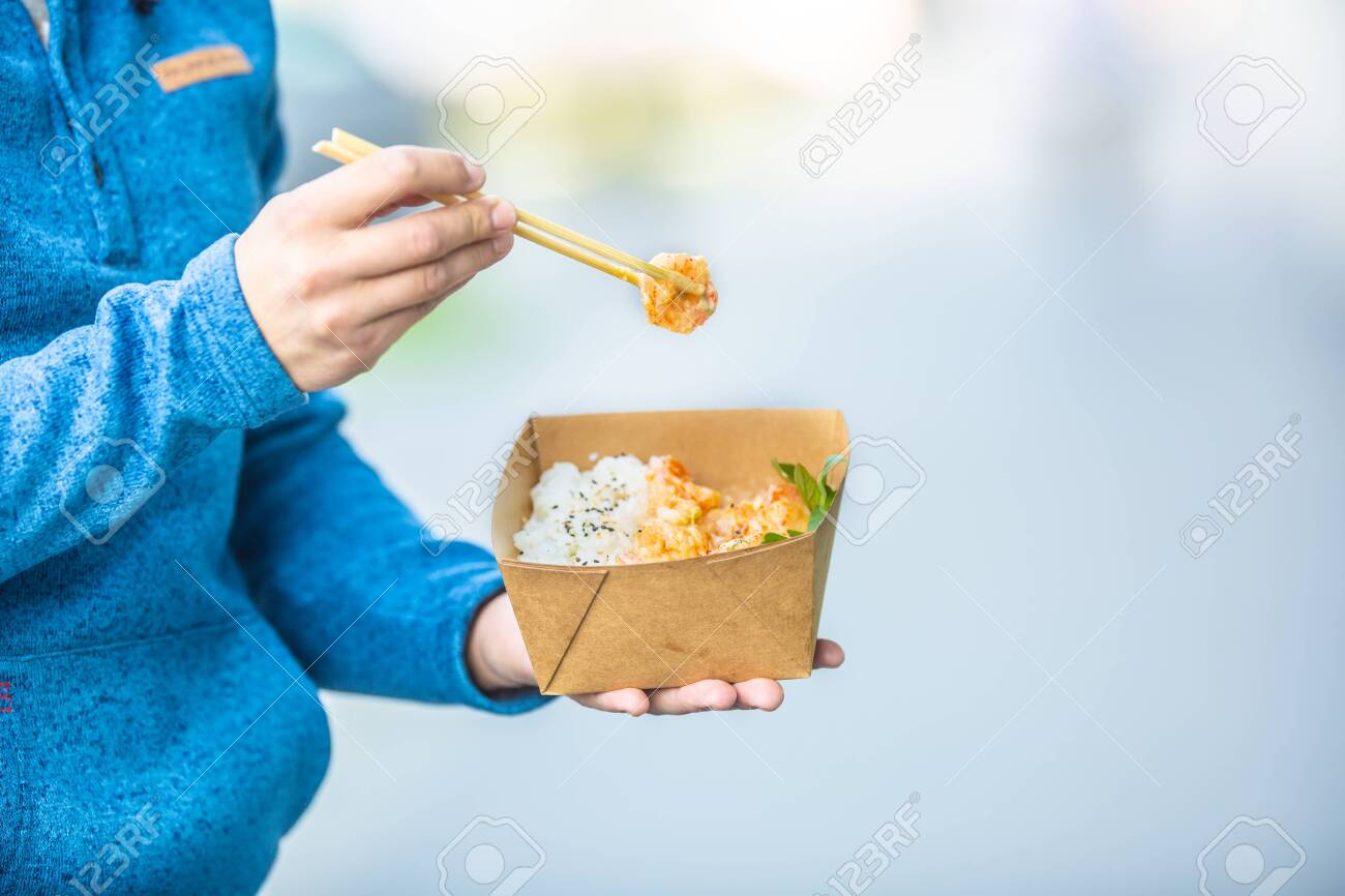 Young mans hands holding lunch in a box of recycled paper. - 130495785