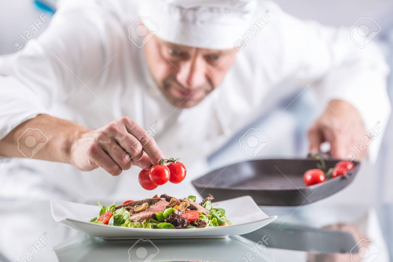 Chef in the kitchen of the hotel or restaurant decorates the food just before serving. - 131089519