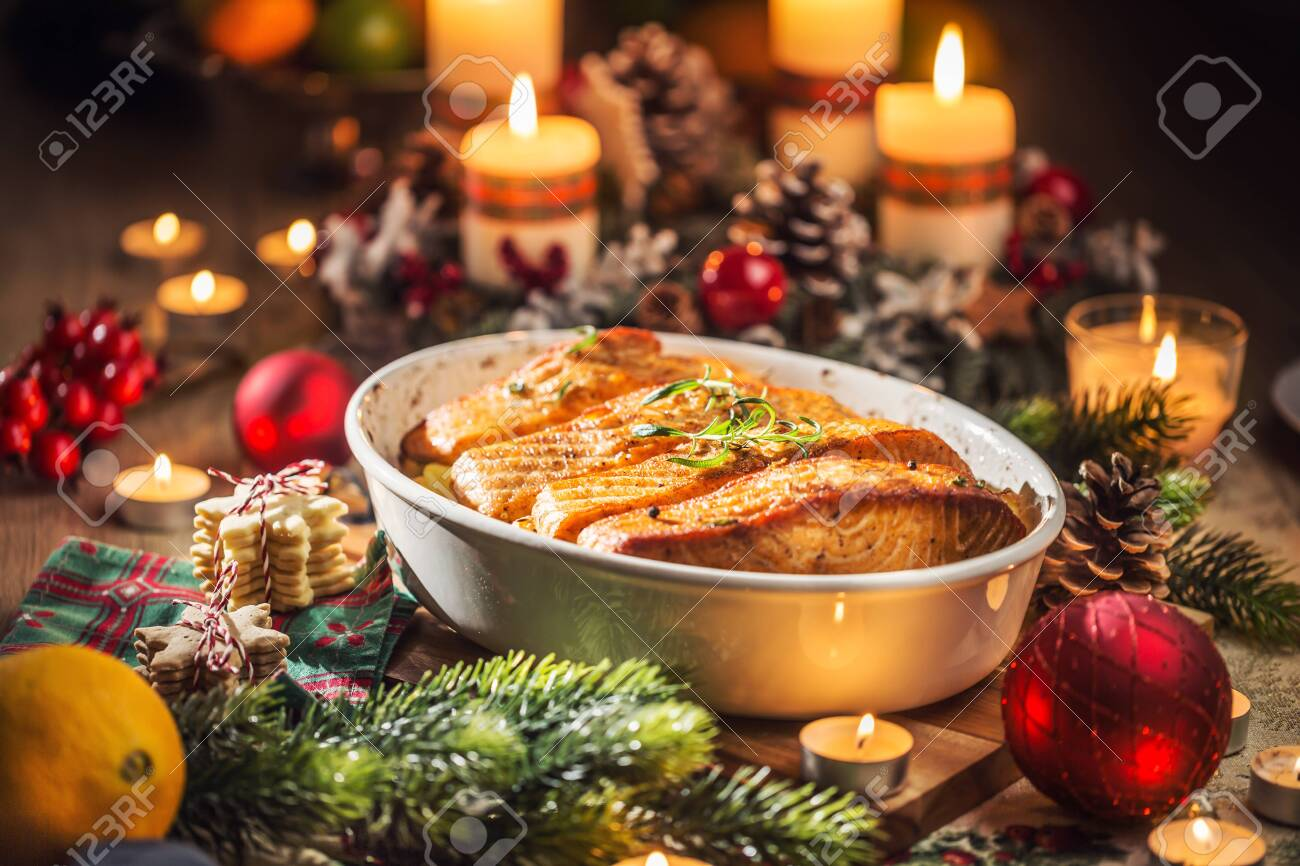 Christmas dinner from fish salmon in roasting dish with festive decoration advent wreath and burning candles . - 135928300