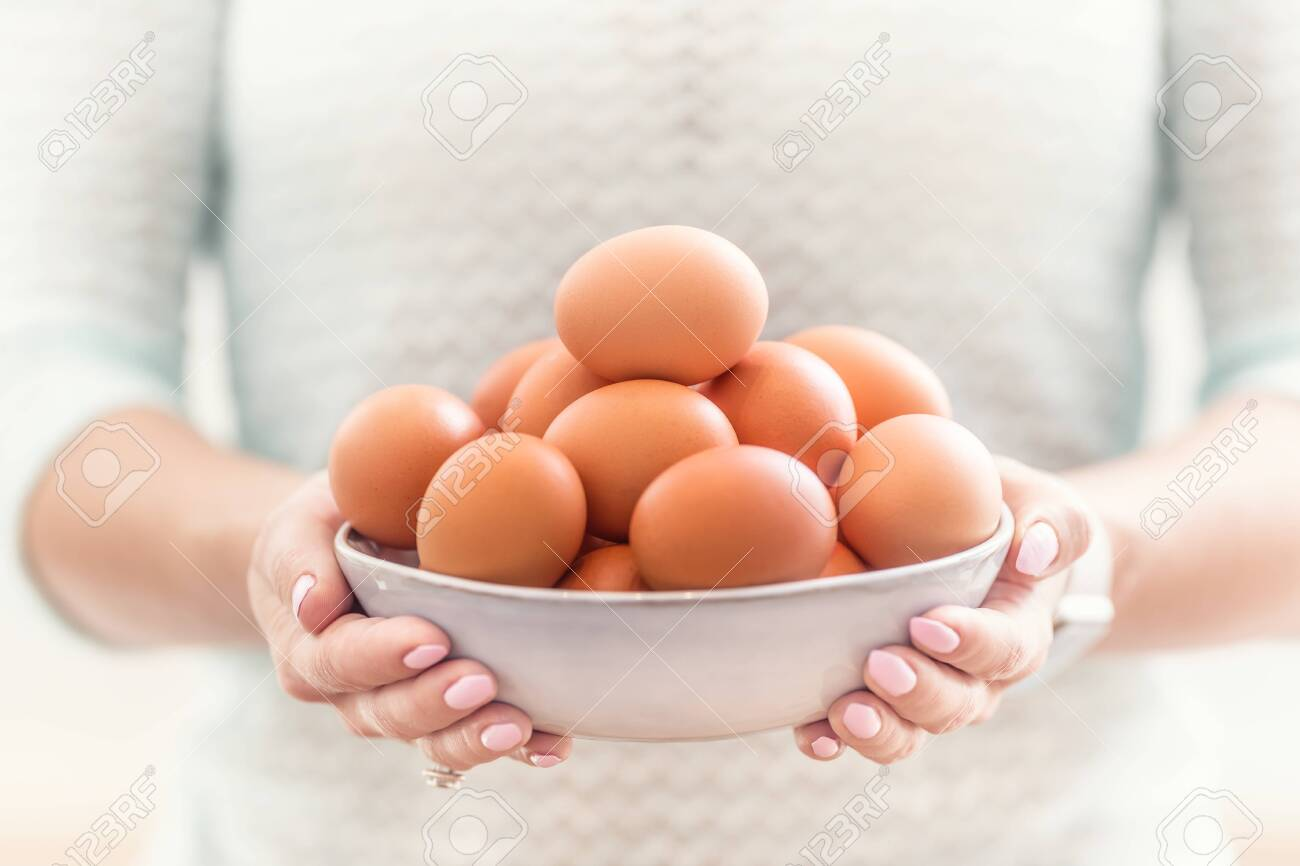 The hands of a young woman hold a bowl of chicken eggs. - 139602371