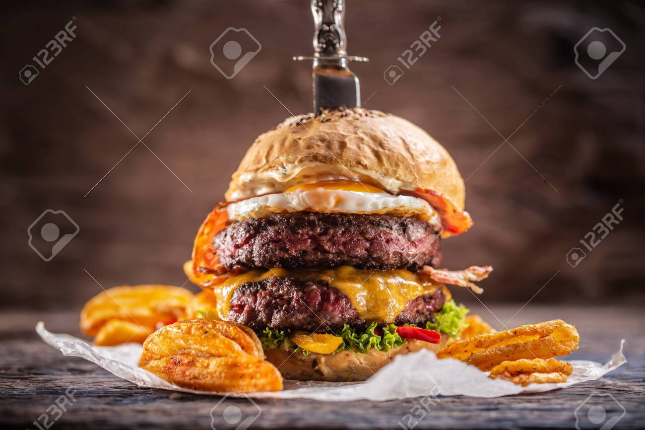 A knife-stabbed double-beef burger with melted cheese, fried egg and bacon, salad and paprika potato wedges. - 148431350