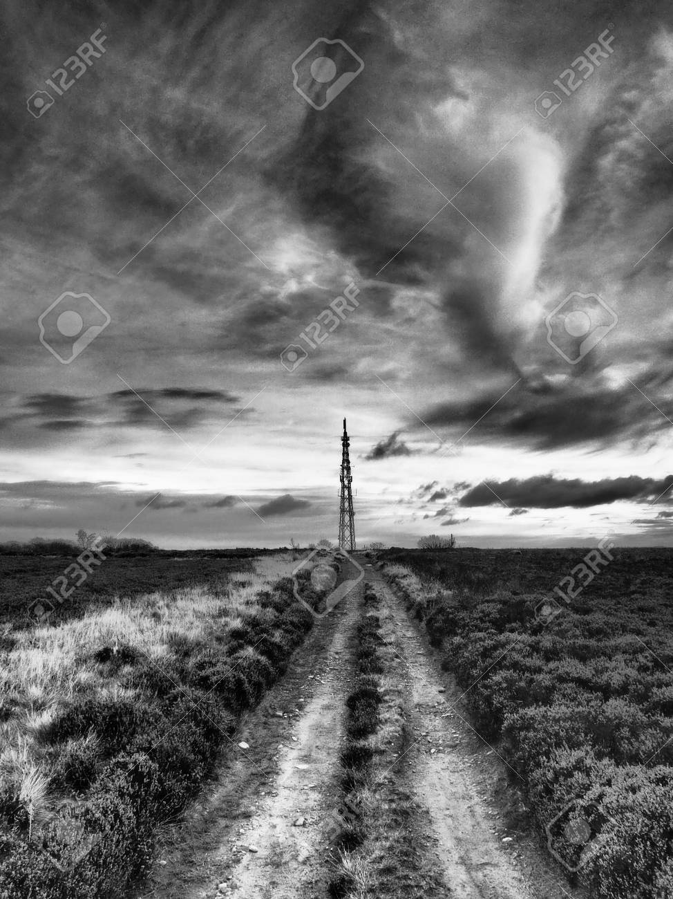 Stock photo transmitter mast viewed from howdale moor under dark menacing brooding sky shot in black and white in the north york moors national park