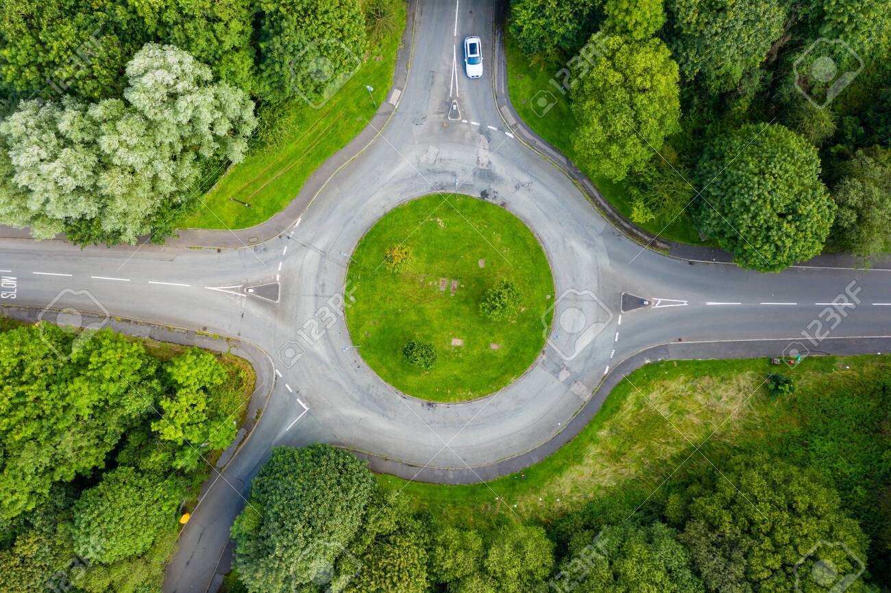 Top down aerial drone view of a small traffic roundabout on a quiet road - 129514241