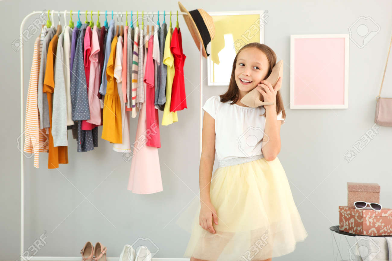 Little cute girl chooses clothes in dressing room - 168600436