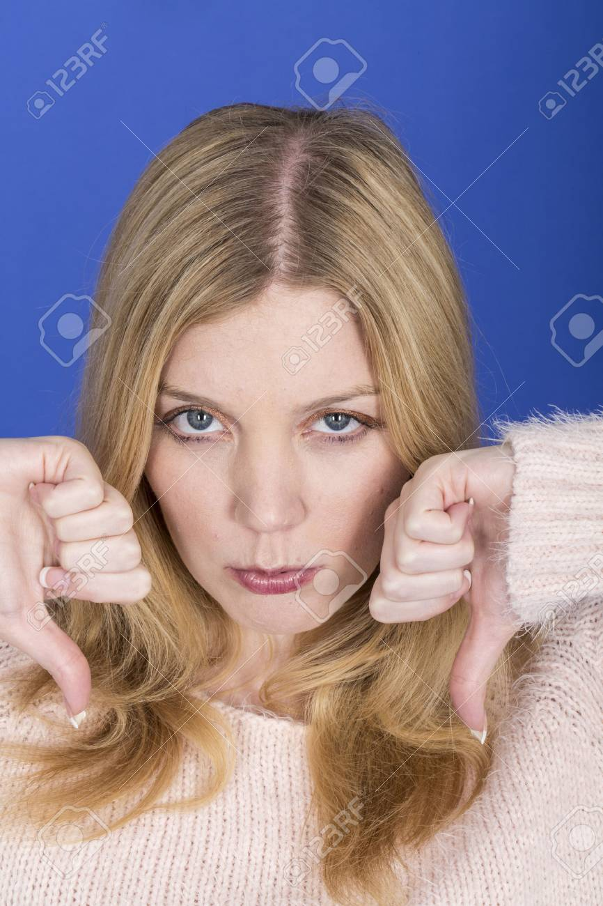 Model Released. Attractive Sad Young Woman Thumbs Down Stock Photo - 22910123