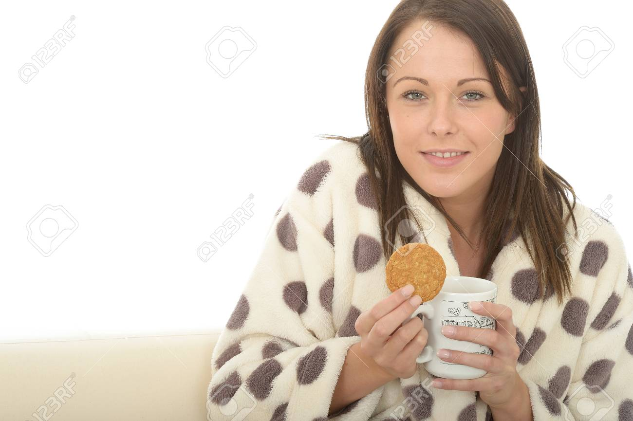 Beautiful Young Woman In A Dressing Gown Enjoying Tea And Biscuits ...