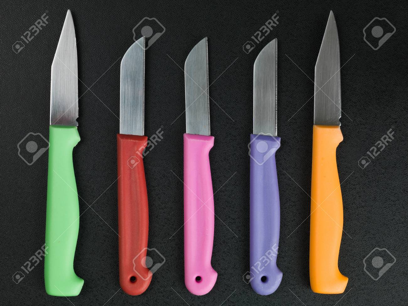Set of Colorful Kitchen Knives Against a Black Background