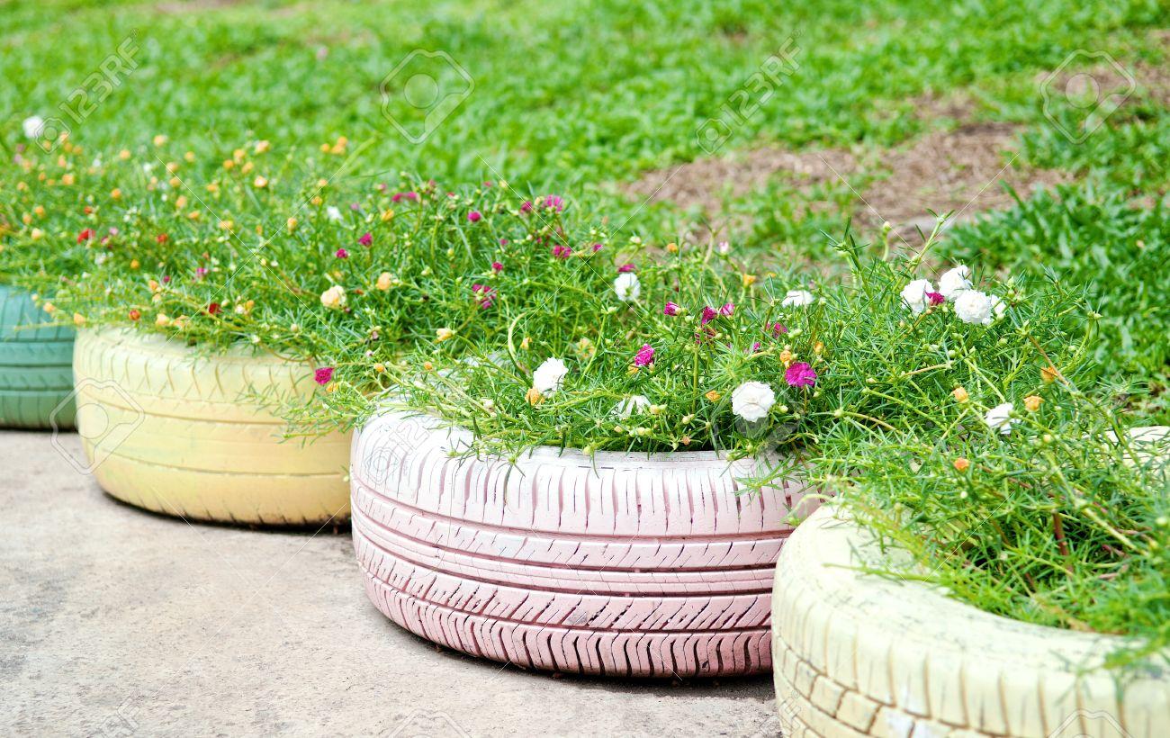 Pot De Fleur Avec Des Pneus recyclage des pneus utilis�s dans un parc public. fleurs et plantes en  vieux pneu peint couleur pastel dans le jardin. conception de caoutchouc