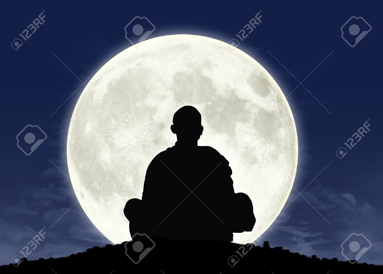 Silhouette Of A Buddhist Monk In Meditation With The Full Moon On Background Stock Photo