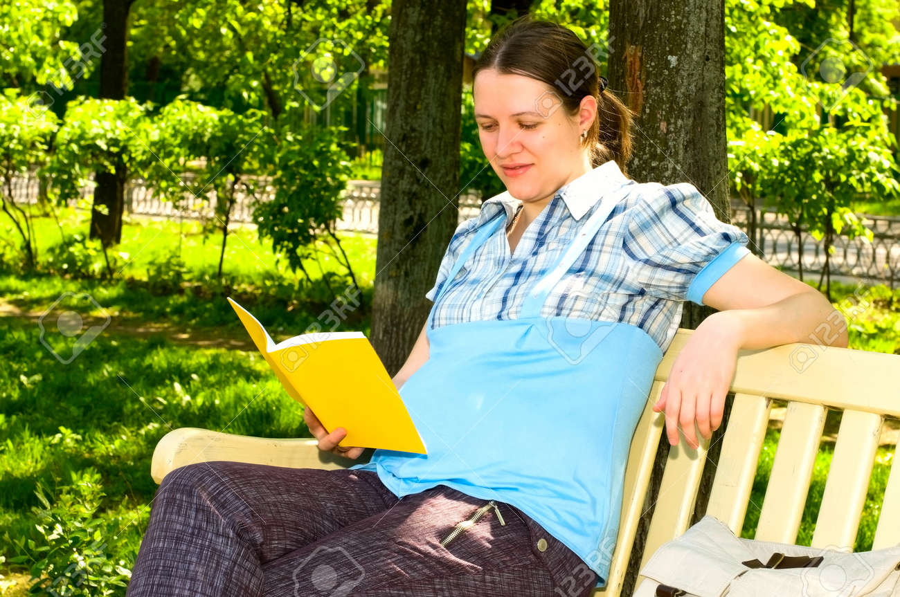 pregnant young woman reading in park Stock Photo - 7097788