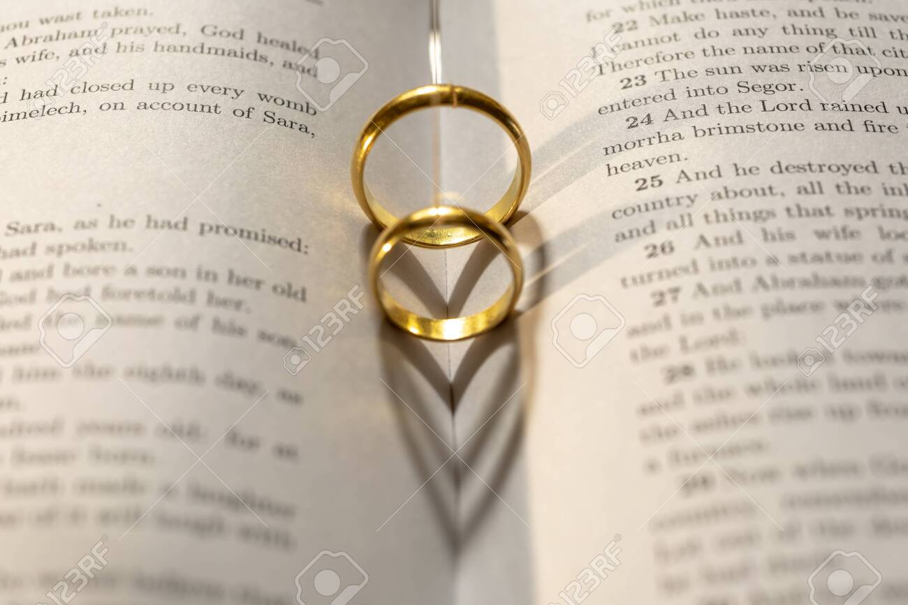 Two wedding Ring on the bible with shadow of heart shape on the page - 147309861