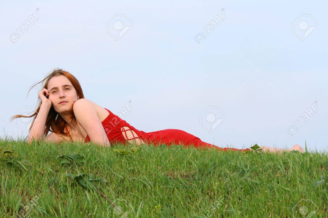 girl in red dress lying on green hillock Stock Photo - 7087116