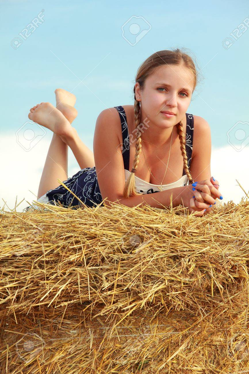 Young attractive barefoot girl lying on a bale of yellow straw Stock Photo - 10750917