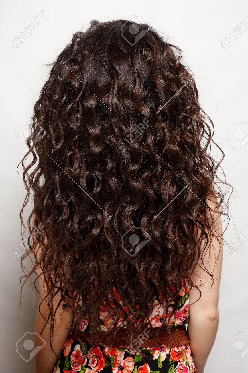 Back Of The Woman With Long Brown Curly Hair With Healthy Shine