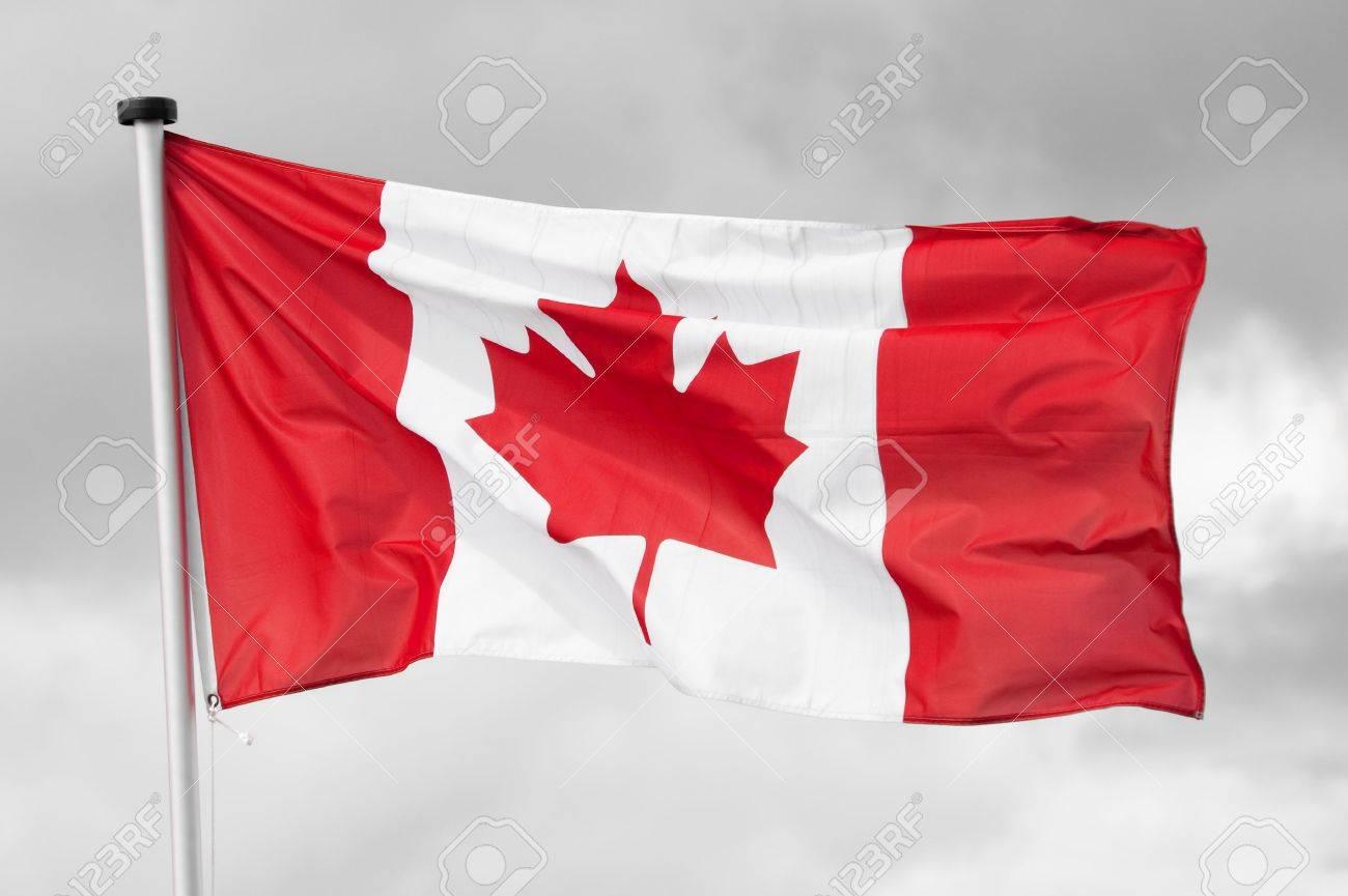 national flag of canada on a black u0026 white cloudy sky background