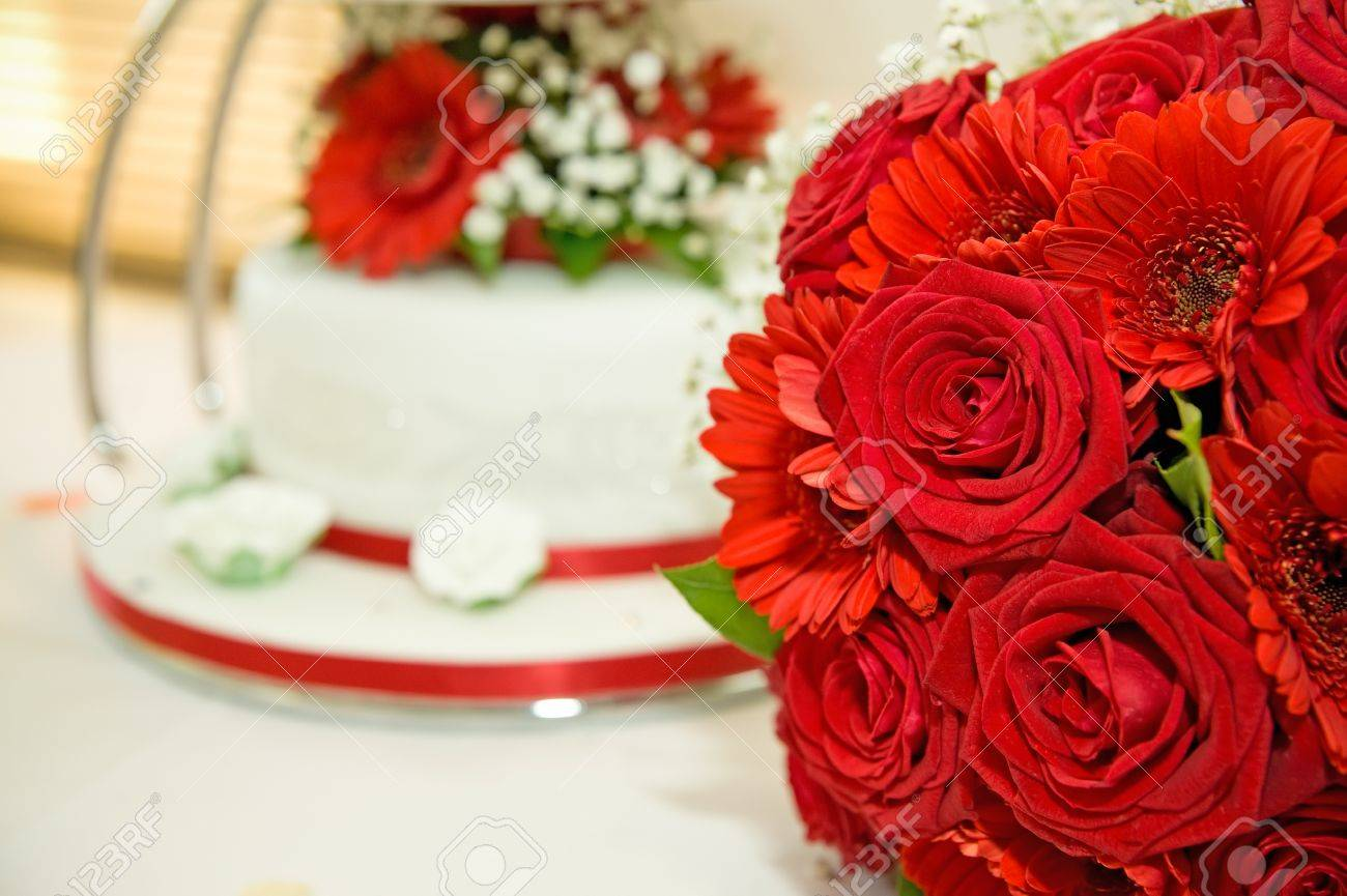 Red Wedding Flowers With Wedding Cake In The Background Stock Photo Picture And Royalty Free Image Image 9751912