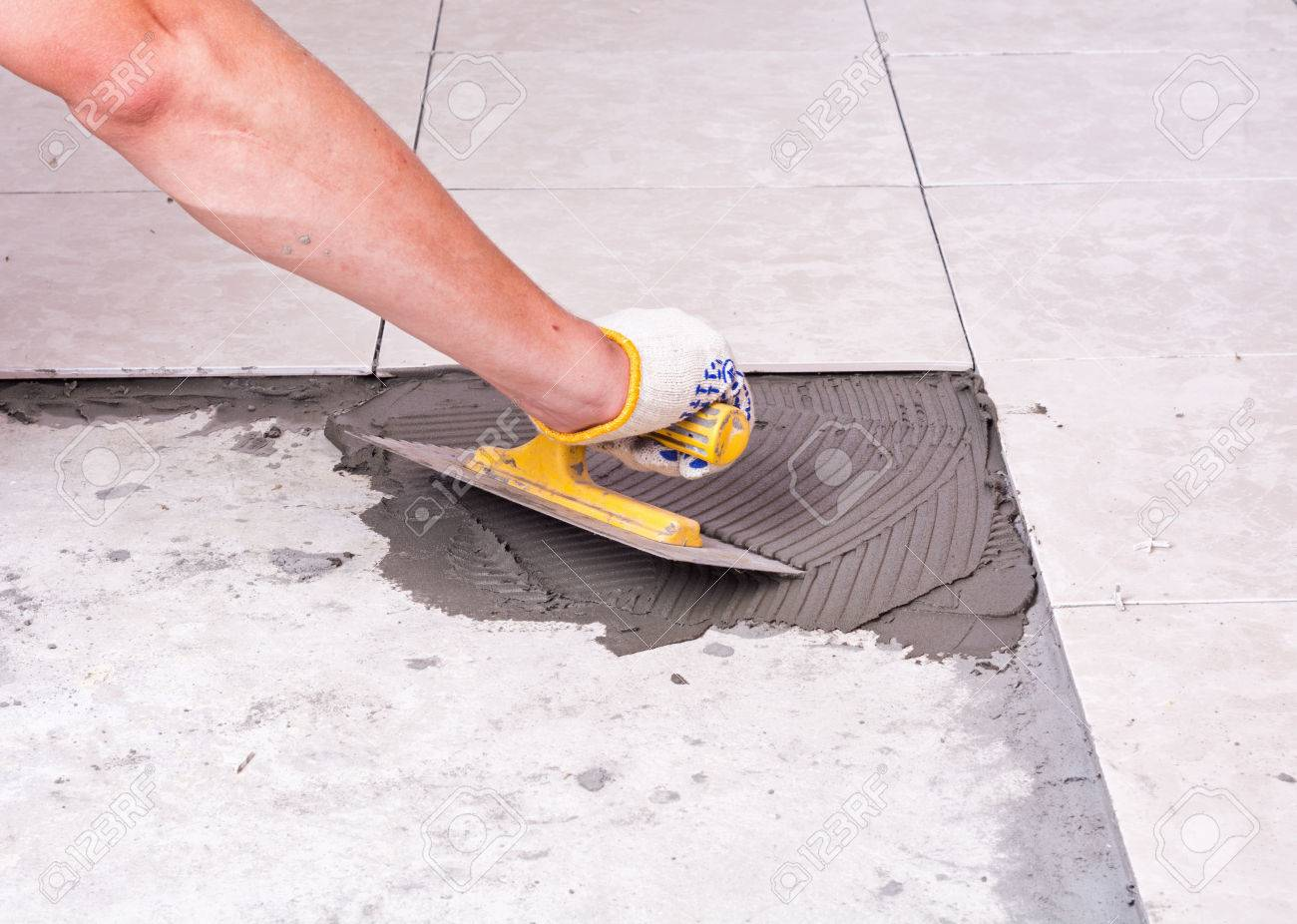 Tiler installing ceramic tiles on a floor stock photo picture and tiler installing ceramic tiles on a floor stock photo 43169103 dailygadgetfo Image collections