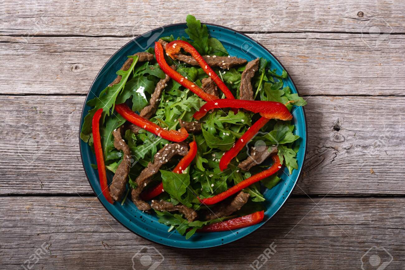 Healthy salad with beef red pepper and arugula. Food on wooden background - 155949373