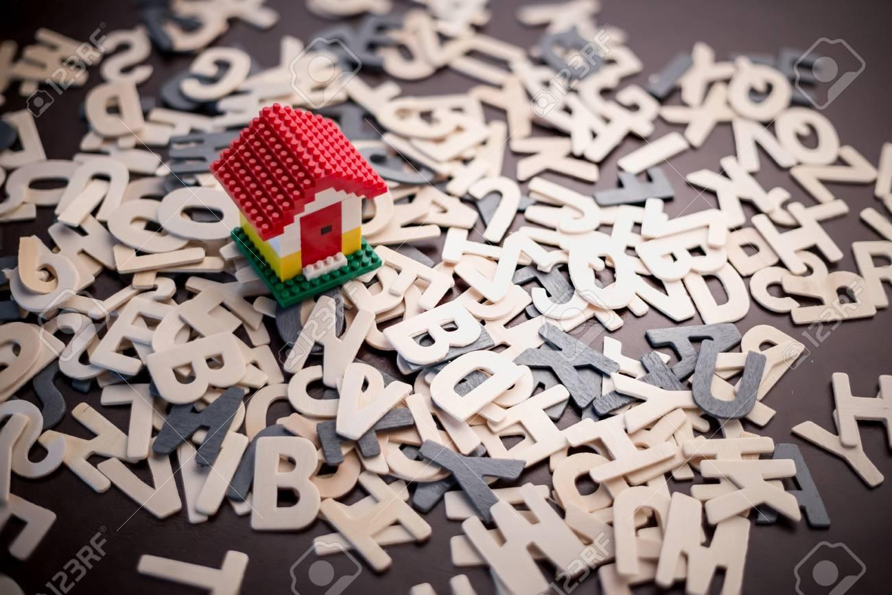 Haus-Konzept Mini Spielzeug Haus Auf Holz-Alphabet Hintergrund ...