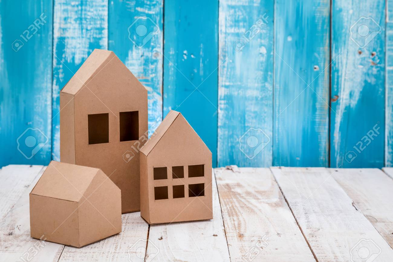 model of cardboard house on wooden floor and background  house
